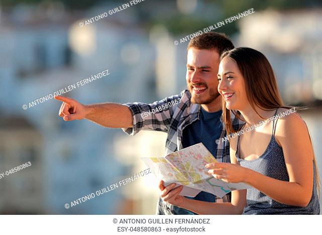 Happy couple of tourists holding paper map pointing away in a town on vacation