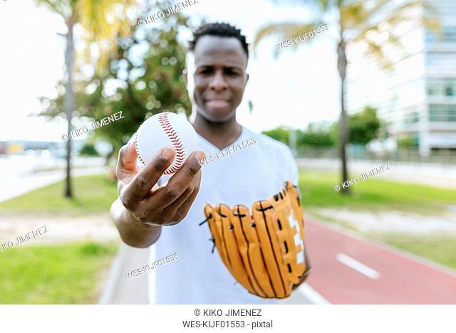 Man's hand holding baseball, close-up