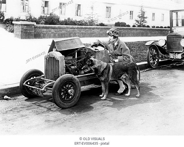 Young woman sitting next to small car looking at the engine with her German shepherd All persons depicted are not longer living and no estate exists Supplier...