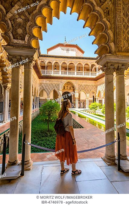 Woman in a Red Dress, Patio de las Doncellas, Court of the Maidens, an Italian Renaissance courtyard, with stucco arabesques in Mudejar style, Alcazar