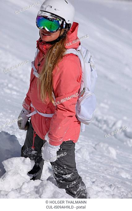 Portrait of young female snowboarder looking up mountain, Hintertux, Tyrol, Austria