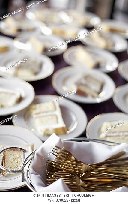 A table laden with plates. White china, and a basket full of dessert forks. A slice of wedding cake