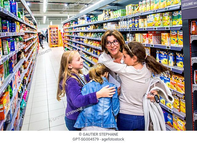 FAMILY HAVING A GOOD TIME SHOPPING AT A SUPERMARKET