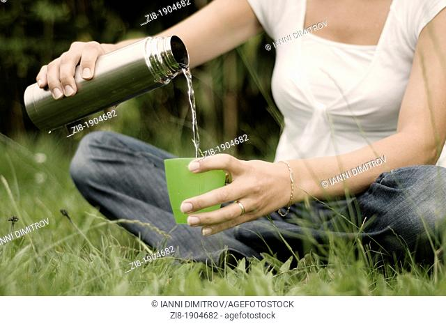 Woman in the park,pouring water from a thermos