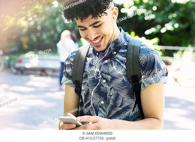 Smiling man with curly black hair listening to music with headphones and mp3 player