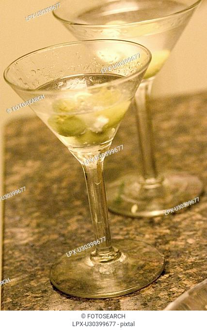 A couple of long stemmed glasses filled with martinis and waiting to be consumed