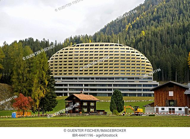 Old Swiss farmhouse in front of modern InterContinental Davos Hotel, Davos, Grisons, Switzerland