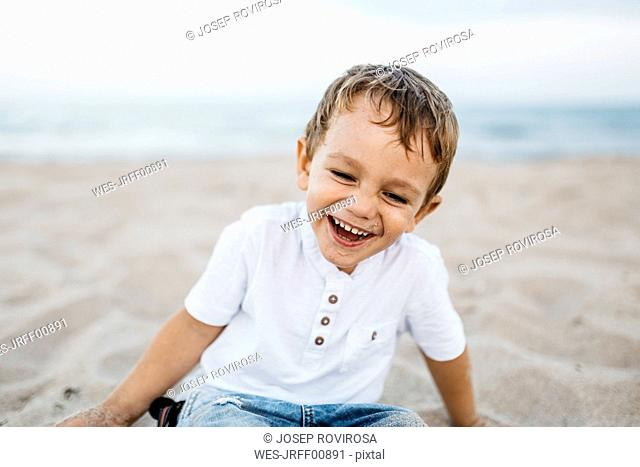 Laughing little boy playing on the beach