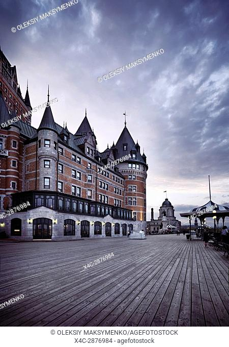 Boardwalk of Dufferin terrace by the Fairmont Le Château Frontenac castle at dusk with dramatic sky, luxury grand hotel Chateau Frontenac