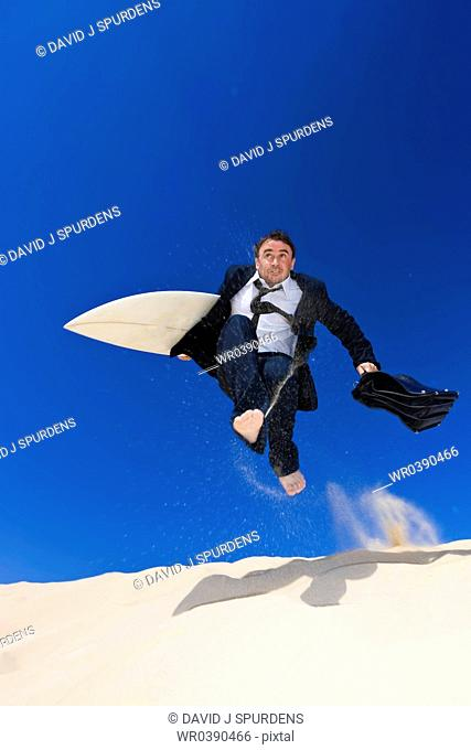 Businessman leaps jumps froma sand dune on way to beach for vacation