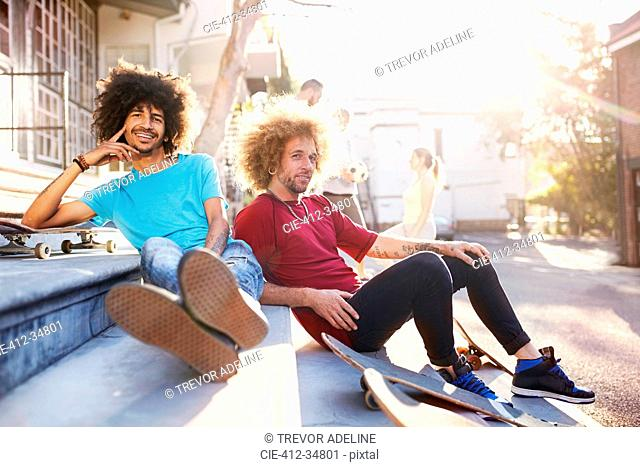 Portrait confident male friends with skateboards hanging out on sunny urban steps