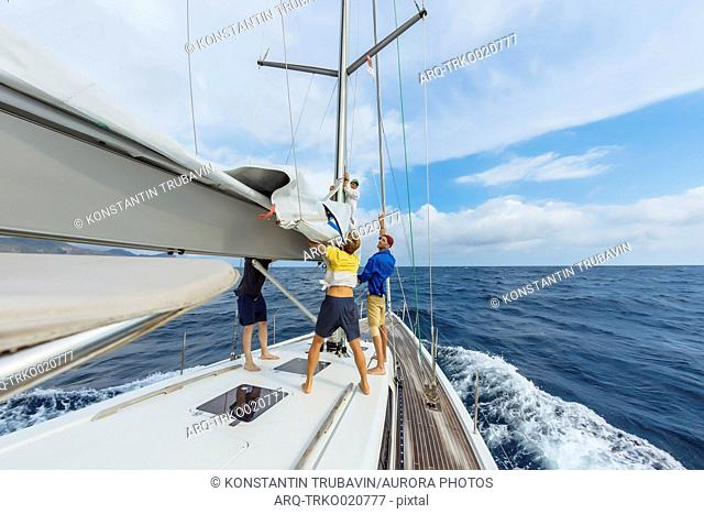 Group of three men busy preparing sailing equipment