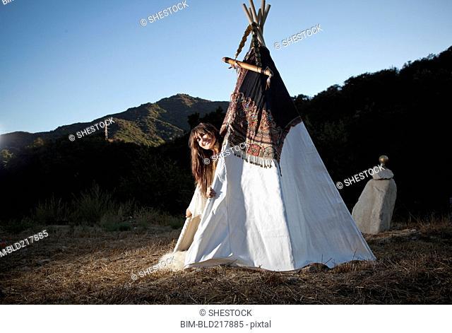 Hispanic woman smiling in teepee in field