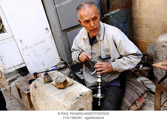 egyptian man cleaning shisha pipes sheesha , a traditional past time in egypt and the middle east , islamic cairo , street scene , cairo , egypt