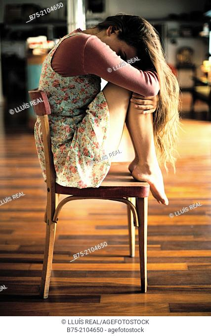 Teenager girl with a country flowers dress seating with the legs on top of the chair and head in his arms thoughtfully fitness