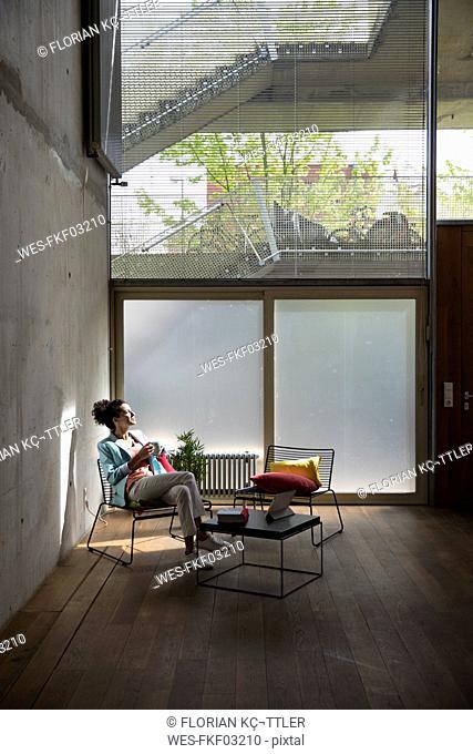 Businesswoman sitting in a loft at concrete wall having a break