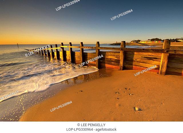 England, Devon, Dawlish, Waves rushing in around wooden sea defences on the Dawlish seafront at dawn