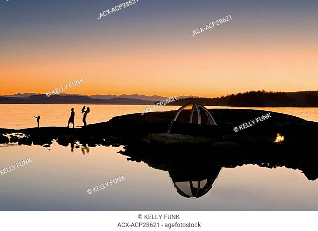 A family enjoys a captivating sunset while camping near Powell River, on the Sunshine coast of the Vancouver coast and mountain region of British Columbia