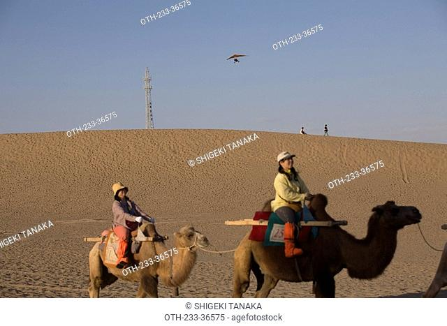 Camel back riding and paragliding on Mingsha Mountain, Dunhuang, China