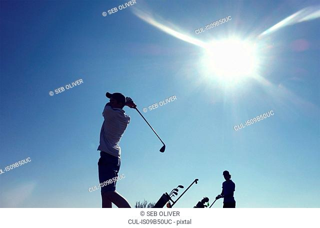 Two boys playing golf
