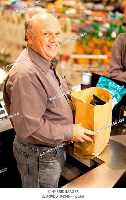 Clerk bagging groceries in store