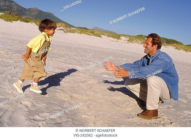 beach-scene, full-figure, man with jeans jacket plays with his 4-year-old brunette son wearing a yellow shirt and beige jumper in the sand  - GERMANY