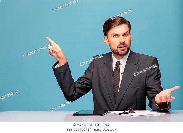 Cheerful young tv newscaster is reporting news. He is sitting at the desk and looking at camera with surprise and question