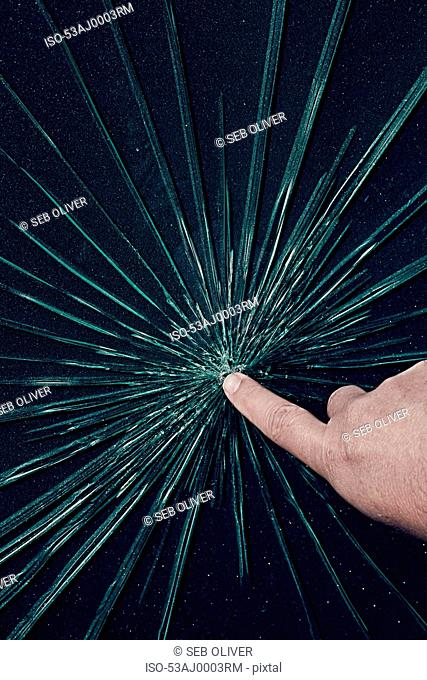 Hand touching cracks in glass