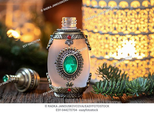 Beautiful essential oil bottle with fresh fir branches and an aroma lamp