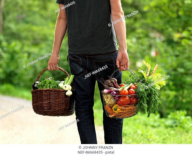 A man carrying baskets full of vegetables Sweden