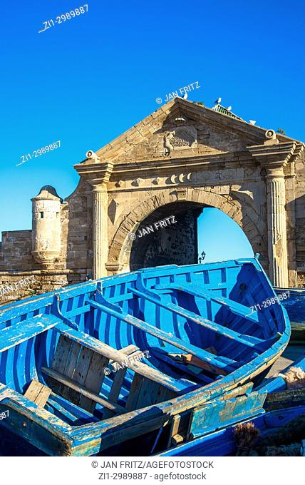 famous blue wooden boat and historic gate in harbour of Essaouira, Maroc