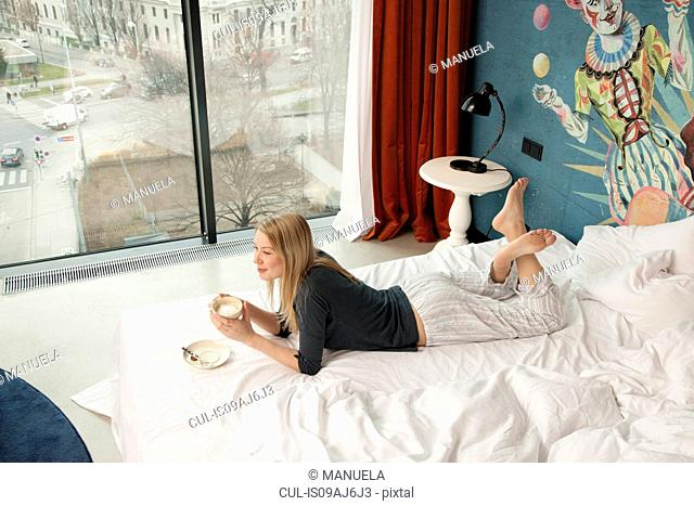 Young woman having a coffee whilst lying on hotel bed