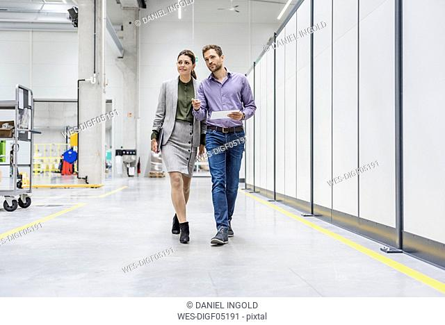 Businessman and woman walking in company, discussing new strategies