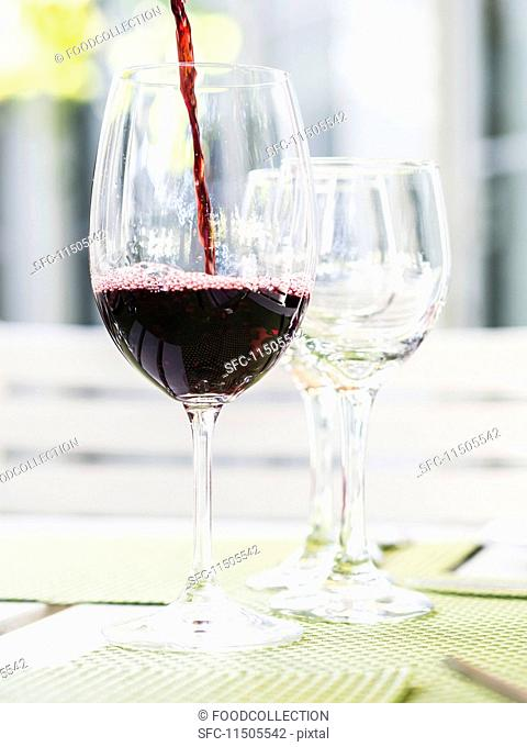Red South African wine being poured into a glass