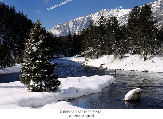 Wading fishermen on Madison River in winter with snowy Rocky mountain Madison Range Montana