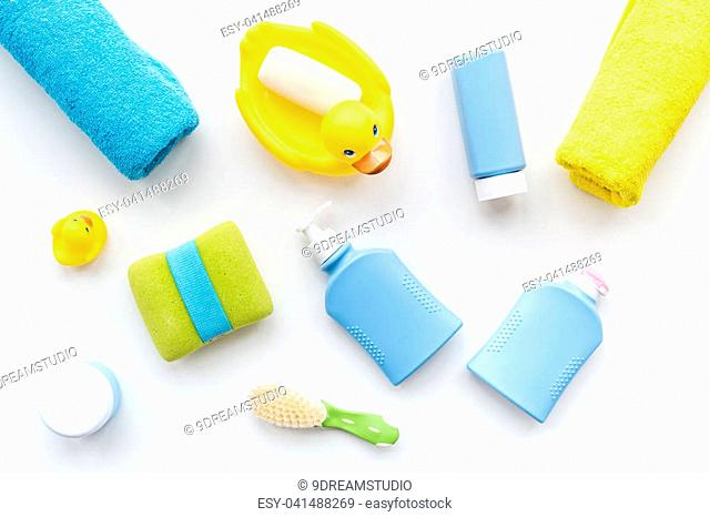 Bath accessories for kids. Yellow rubber duck, soap, sponge, brushes, towel on white background top view