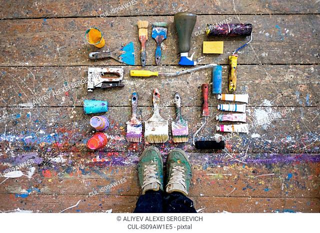 Overhead view of artists feet and art equipment on paint splashed floorboard