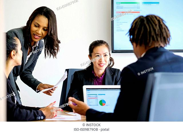 Businessman and businesswomen, in office meeting, using laptop, looking at data