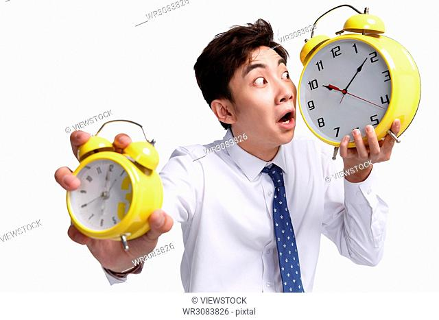 Shocking business young man with an alarm clock