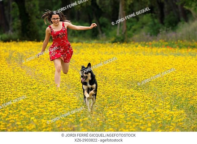 Girl with a red dress running with a dog in a yellow field