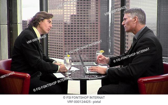 TD, MS, Two businessmen having a meeting at a hotel dining table