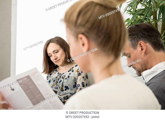 Three people sitting in waiting area of hospital, Munich, Bavaria, Germany