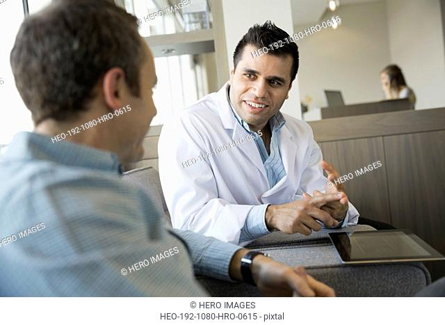 Dentist talking with patient in lobby