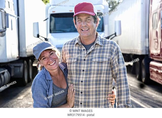 Husband and wife driving team in front of their commercial truck at a truck stop