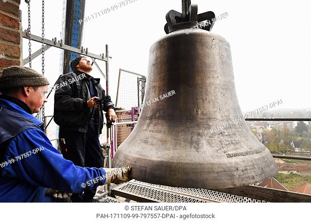 Bell technician Udo Griwahn and Mathias Heitmann (L-R) transport a 1.7 ton heavy bronze bell into the tower of the St. Petri church in Wolgast, Germany