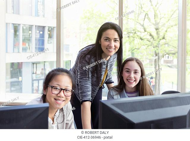 Portrait confident, smiling female teacher and girl students researching at computer in library