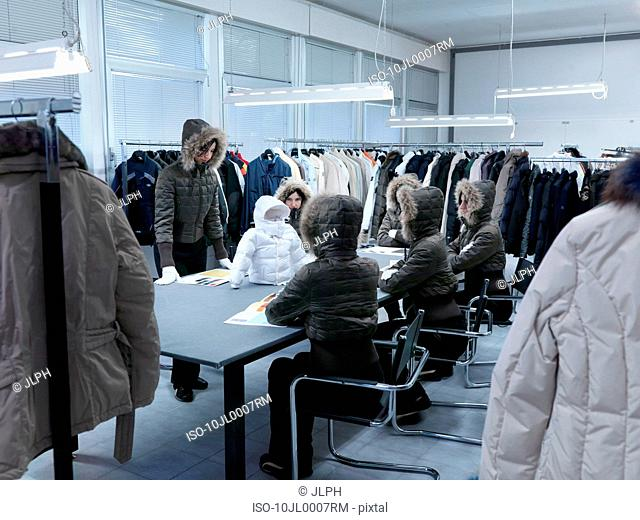 Product developers inspecting coat
