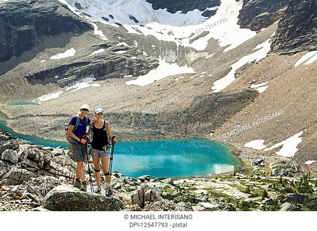 Two female hikers standing in a large rocky area with a colourful alpine lake and mountain cliffs with snow in the background; British Columbia, Canada