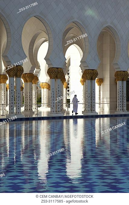 Local man in traditional clothing between the gilded columns of Sheikh Zayed Bin Sultan Al Nahyan Mosque, Abu Dhabi, United Arab Emirates, Middle East