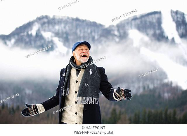 Portrait of happy senior man in winter landscape